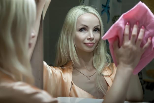 女性がバスルームの鏡を拭きます。かわいい女の子が家を掃除します。家でぼろきれで掃除するかわいい女性。完璧な反射。布とエージェントできれいな女性。コンセプト家庭用クリーニングまたはクリーニングサービス