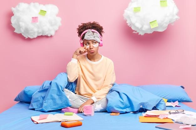 寝間着を着た女性が涙を拭く 仕事が多すぎて気分が台無しになっている ベッドに残っている ワイヤレスヘッドホンで音楽を聴く エッセイを書く ステッカーにメモを書く