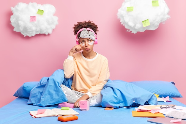 Woman wipes tears dressed in nightwear has spoiled mood because of much work stays at bed listens music via wireless headphones writes essay makes notes on stickers