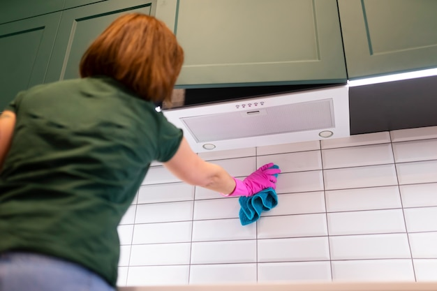 Woman wipes tiles in the kitchen.