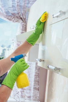 A woman wipes with a yellow cloth the kitchen cabinet, using a chemical from a bottle