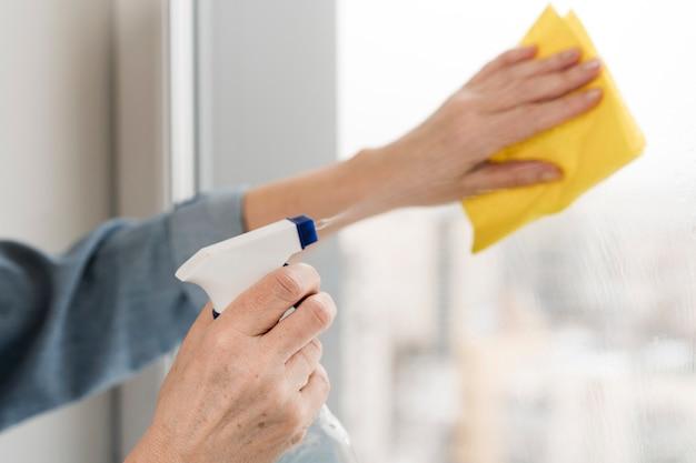 Женщина вытирает и распыляет окно