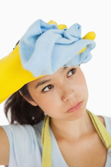 Woman wiping her brow wearing rubber gloves and an apron