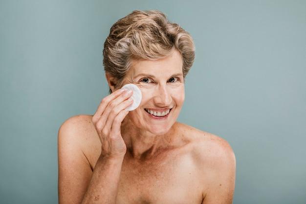 コットンパッドで顔を拭く女性