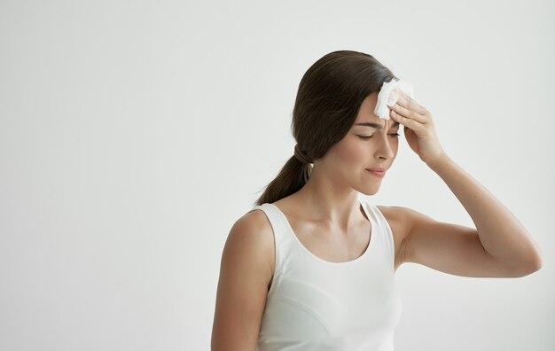 体調不良の風邪をひいたハンカチで顔を拭く女性