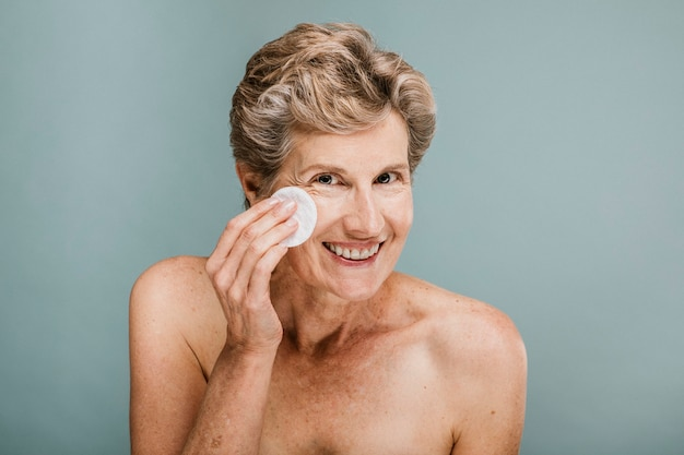 Woman wiping her face with a cotton pad