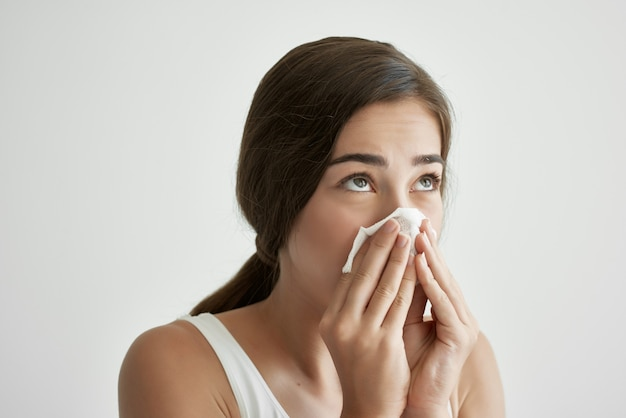 Женщина, вытирая нос платком, холодное расстройство здоровья