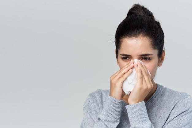 Женщина, вытирая нос платком, лечение проблем со здоровьем