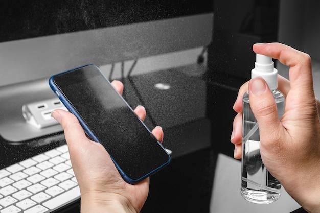 Женщина обтирая экран мобильного телефона с дезинфицирующим средством на деревянной предпосылке. очистка экрана смартфона для предотвращения вируса короны covid 19