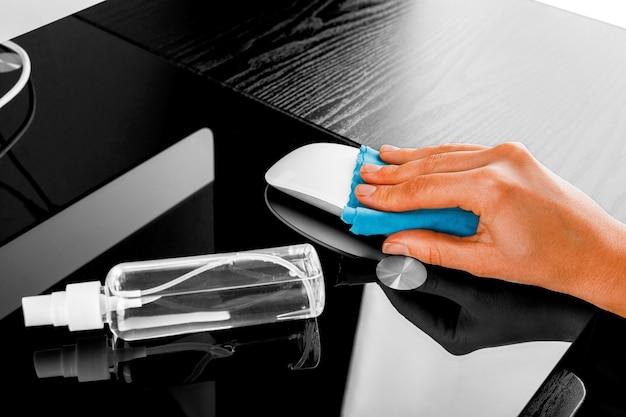 Женщина вытирая экран мобильного телефона с дезинфицирующим средством на деревянной предпосылке. очистка экрана смартфона от вируса короны covid 19