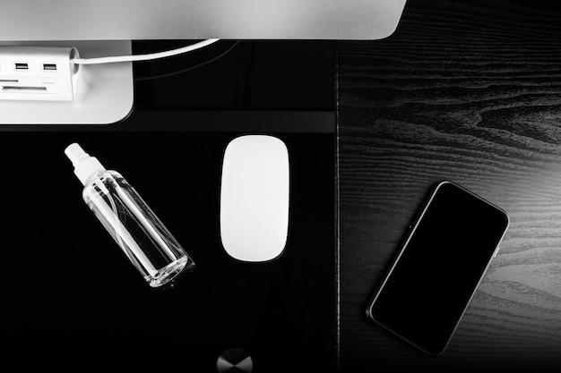 Женщина вытирая экран мобильного телефона с дезинфицирующим средством на дереве. очистка экрана смартфона от вируса короны covid 19