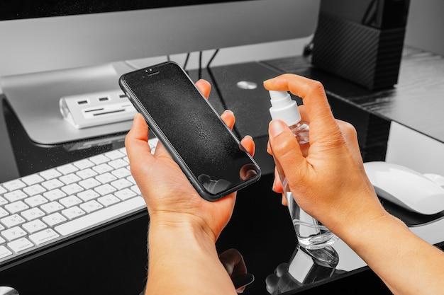 Женщина протирает экран мобильного телефона с дезинфицирующим средством