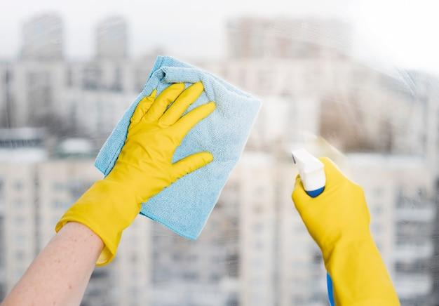Женщина вытирает окно тряпкой