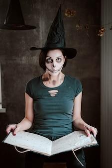 女性の魔女のコスチュームとスケルトンメイクは、ハロウィーンの魔女のための黒い魔法の本を開きます。コスチュームパーティー、ウォーロック
