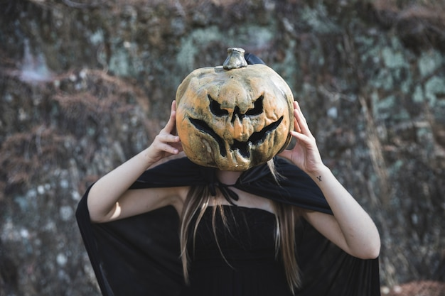 Woman in witch costume closing face by frightful pumpkin