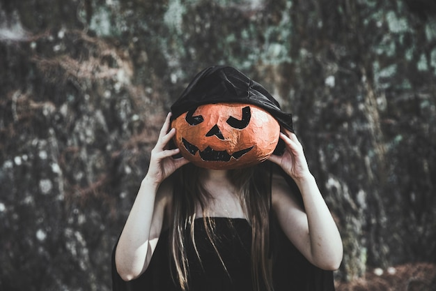Woman in witch costume closing face by pumpkin