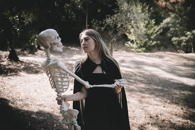 Woman in witch costume holding accuracy skeleton