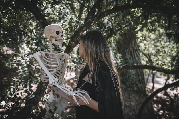 Woman in witch costume holding creepy skeleton