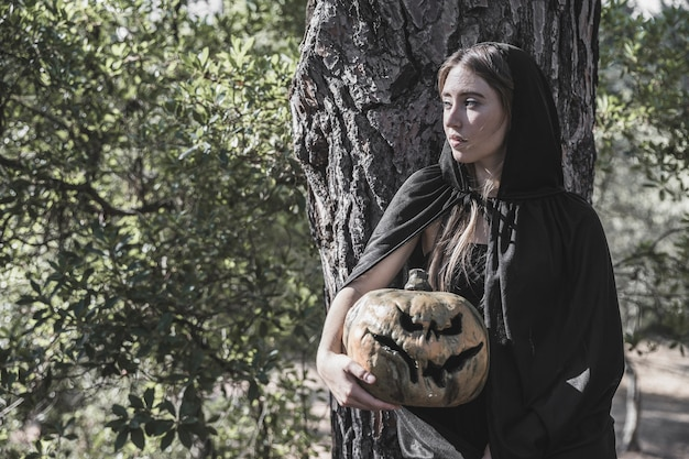 Woman in witch costume holding frightful pumpkin leaning on wood