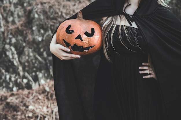 Woman in witch costume holding pumpkin