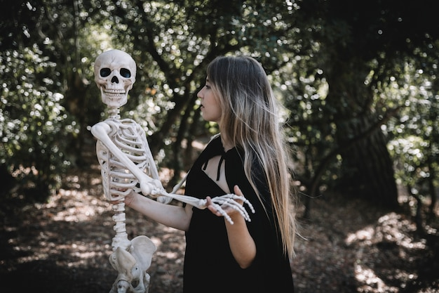 Woman in witch costume holding skeleton