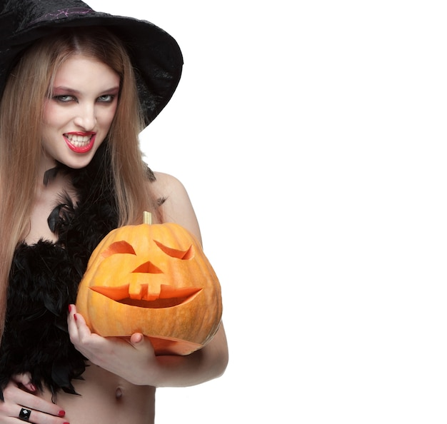Woman in witch costume opens carved halloween pumpkin and space for text