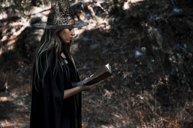Woman in witch costume reading book