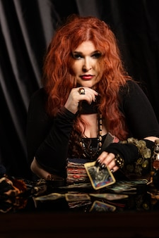 Woman witch, fortune teller with red hair performs a magical ritual. card reading.