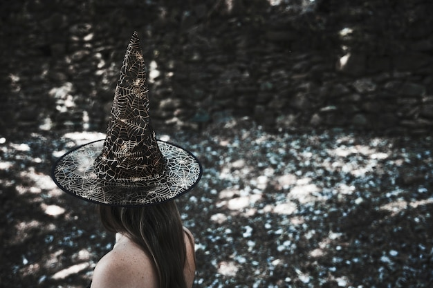 Woman in witch hat standing in forest