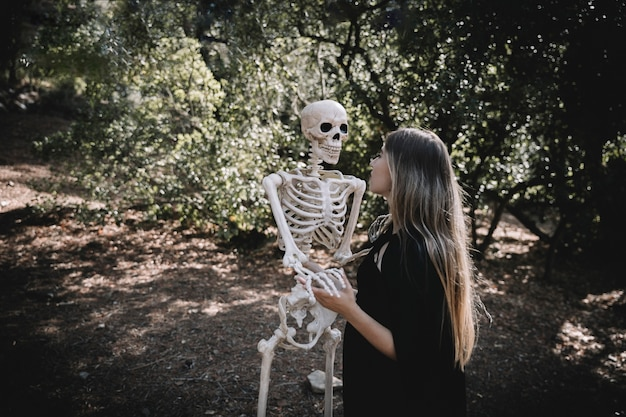 Woman in witch suit holding and looking attentive at skeleton