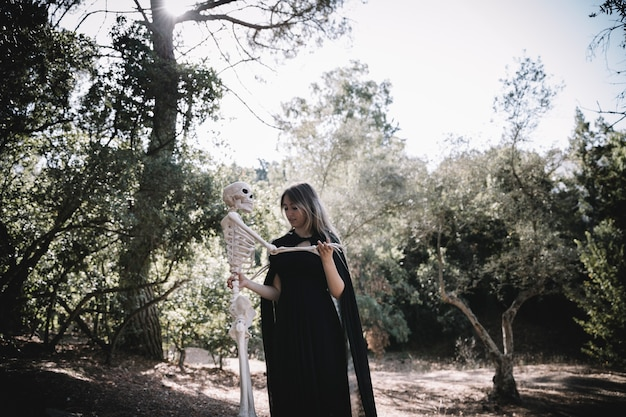 Woman in witch suit holding skeleton