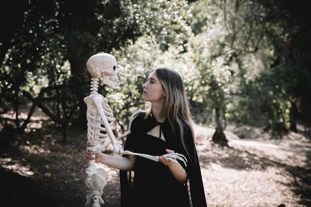 Woman in witch suit looking attentive at skeleton