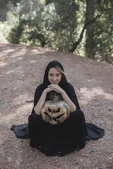 Woman in witch suit sitting on soil and holding pumpkin
