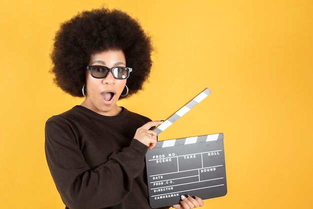 Woman with 3d glasses and clapperboard on color surface. cinema show