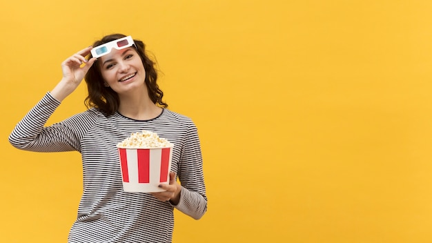 Woman with 3d glasses holding a bucket with popcorn with copy space