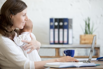 Woman with a baby looking at his laptop