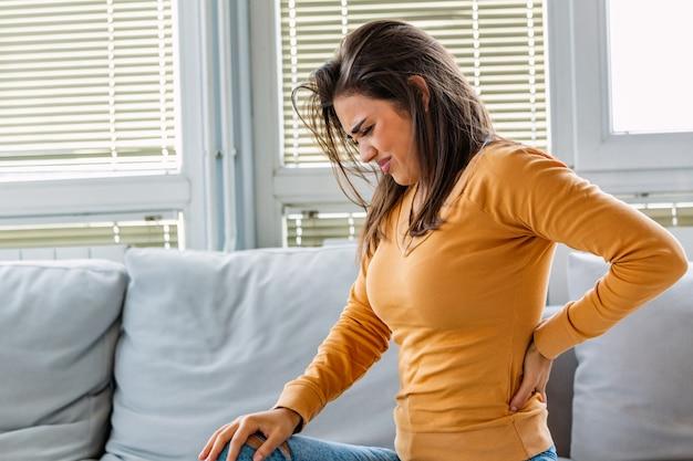 Женщина с болями в спине, сидя на диване