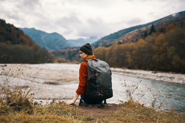 自然の山の川岸にバックパックと帽子をかぶったジャケットを着た女性
