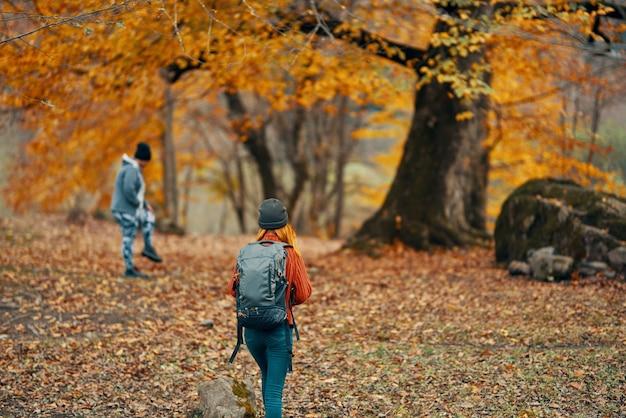 バックパックを持った女性が自然の風景の木の通行人モデルの秋の森を歩いています