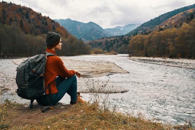 山の側面図の川岸にジャケットと帽子のバックパックを持つ女性