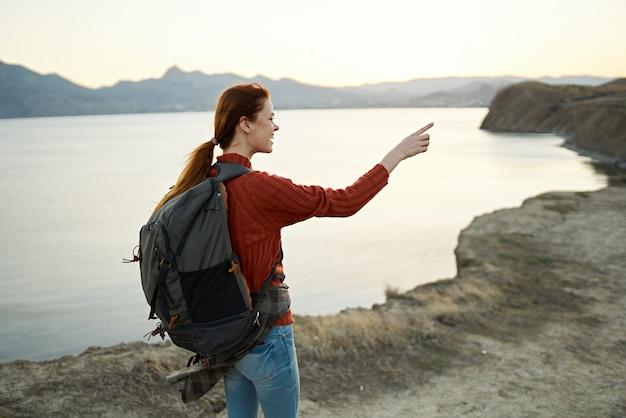 山の中で赤いセーターを着たバックパックを持つ女性