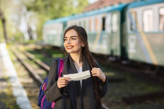 Женщина с рюкзаком, возле поезда проверяет свой билет на платформу вокзала