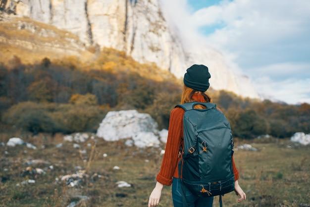 バックパックを持つ女性は、秋の青い空の岩の風景の中の山の自然の上を歩きます
