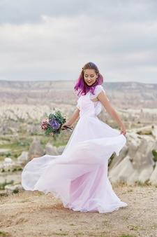 彼女の手に美しい花束を持つ女性は、夜明けの夕日の光線で山の上で踊ります。女の子の体に美しい白いロングドレス。ピンクの髪のダンスと完璧な花嫁