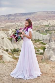 그녀의 손에있는 꽃의 아름 다운 꽃다발을 가진 여자