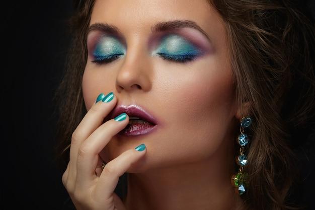 美しい化粧と光沢のあるイヤリングを身に着けている髪型の女性