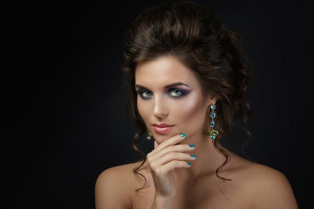 Женщина с красивым макияжем и прической в блестящих серьгах