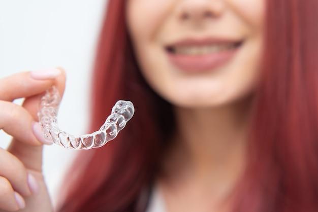 Женщина с красивой улыбкой показывает прозрачную каппу