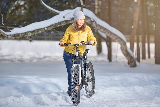 冬に自転車を持っている女性。ウィンタースポーツ。アクティブなレクリエーション。