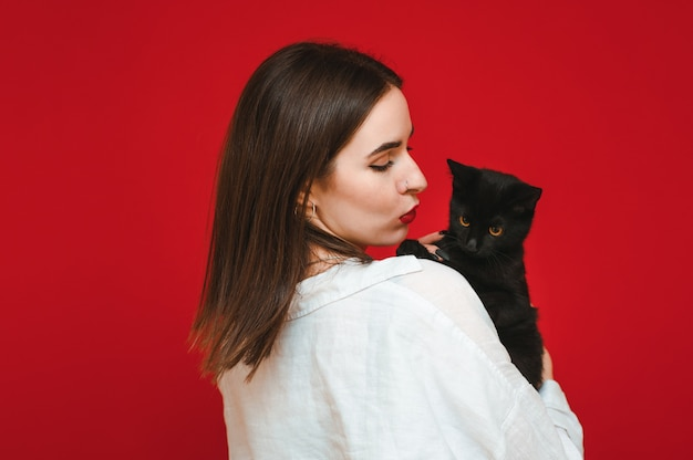 Женщина с черной милой кошкой на руках смотрит на любителя домашних животных